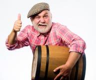 Concetto della cantina Vino casalingo Produzione della tradizione della famiglia del vino L'anziano barbuto dell'uomo porta il ba fotografia stock