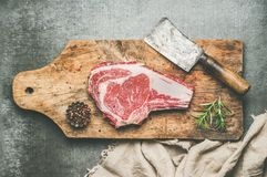Concetto della cena della carne con l'costola-occhio crudo della bistecca di manzo con condimento Immagini Stock