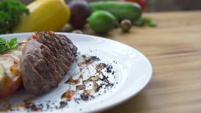 Concetto della composizione degli alimenti Carne arrostita con il contorno di verdure sulla tavola di legno in ristorante Designa archivi video