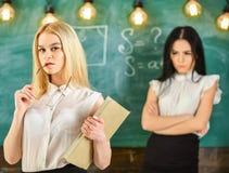 Concetto della concorrenza e di invidia La donna con il libro e gli occhiali sembra vaga mentre lo studente su fondo sembra gelos Fotografia Stock