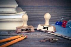 Concetto della copia e di originale Timbro di gomma sullo scrittorio nell'ufficio Fondo del lavoro e di affari Immagini Stock
