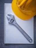 Concetto della costruzione della chiave regolabile del casco del taccuino Immagine Stock