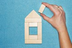 Concetto della costruzione e di assicurazione la mano costruisce la casa dei cubi di legno su fondo blu Riparazione e ripristino  immagini stock libere da diritti