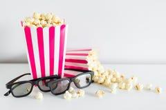 Concetto della data e del cinema - fine su di due scatole a strisce con popcorn, vetri 3d e lo spazio della copia sopra bianco fotografia stock