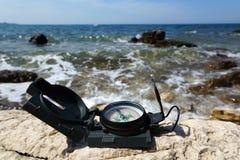 Concetto della destinazione di festa con la bussola sul mare Fotografie Stock Libere da Diritti