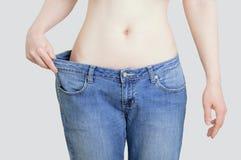 Concetto della dieta e della perdita di peso Donna in grandi jeans su fondo grigio pastello fotografie stock