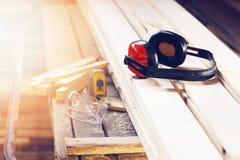 Concetto della fabbrica della segheria Cuffie, vetri di protezione e nastro-misura protettivi sul posto di lavoro fotografie stock