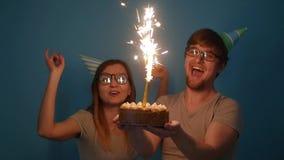 Concetto della festa e del compleanno Giovani coppie divertenti allegre divertendosi con la torta di compleanno archivi video