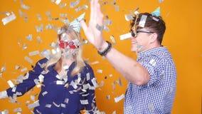Concetto della festa e del compleanno Giovani coppie felici che ballano in cappelli su fondo arancio con i coriandoli video d archivio