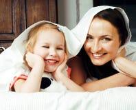 Concetto della gente di stile di vita: madre sorridente felice con la piccola figlia sveglia divertendosi a letto Fotografia Stock Libera da Diritti