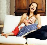 Concetto della gente di stile di vita: madre sorridente felice con la piccola figlia sveglia divertendosi a letto Fotografia Stock
