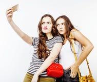 Concetto della gente di stile di vita: ragazza teenager dei pantaloni a vita bassa moderni abbastanza alla moda due divertendosi  fotografia stock