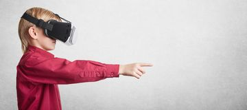 Concetto della gente, di tecnologia e di progresso Il piccolo ragazzo emozionante indossa 3D i vetri futuristici, la realtà virtu Fotografie Stock