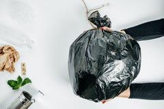 Concetto della gestione dei rifiuti Mani della donna con immondizia sul bianco Immagini Stock