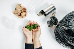Concetto della gestione dei rifiuti Mani della donna con la foglia e il garbag verdi Immagini Stock Libere da Diritti