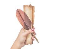 Concetto della letteratura La mano femminile della donna tiene una penna di spoletta della piuma con il vecchio rotolo d'annata i Immagini Stock