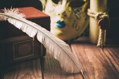 Concetto della letteratura Metta le piume a sul libro vicino alla maschera veneziana e sul vecchio rotolo su fondo di legno fotografia stock libera da diritti