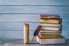 Concetto della letteratura Piuma di Brown vicino al vecchi rotolo e pila di vecchi libri contro fondo di legno blu immagini stock libere da diritti