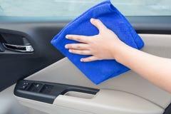 Concetto della mano che pulisce il pannello interno della porta di automobile con il microfiber Fotografie Stock Libere da Diritti