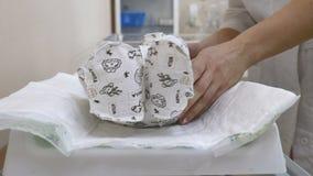 Concetto della maternità L'infante irriconoscibile è sulla tavola che si prepara per le procedure mediche Vaccinazione neonata video d archivio