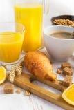 Concetto della prima colazione - caffè, croissant e succo d'arancia su un briciolo Immagini Stock