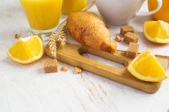 Concetto della prima colazione - croissant, succo d'arancia e caffè su un briciolo Immagine Stock