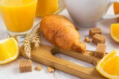 Concetto della prima colazione - croissant, succo d'arancia e caffè su un briciolo Immagini Stock