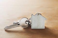 Concetto della proprietà con il simbolo della casa, chiave su fondo di legno fotografie stock libere da diritti