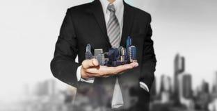 Concetto della proprietà del bene immobile, agente immobiliare di affari che tiene le costruzioni moderne a disposizione Immagini Stock