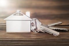 Concetto della proprietà, keychain con il simbolo della casa, chiave su fondo di legno Immagine Stock Libera da Diritti