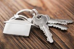 Concetto della proprietà, keychain con il simbolo della casa, chiave su fondo di legno Immagini Stock Libere da Diritti