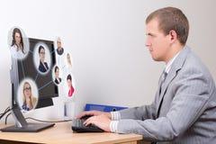 Concetto della rete sociale - giovane uomo di affari che lavora nell'ufficio fotografia stock