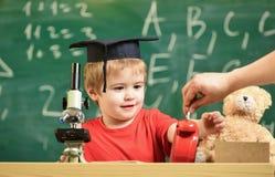 Concetto della rottura della scuola Il bambino sul fronte sorridente esamina la sveglia Rottura aspettante della scuola dell'alli Immagine Stock Libera da Diritti