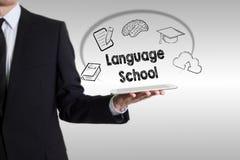 Concetto della scuola di lingue con il giovane che tiene un computer della compressa immagine stock libera da diritti