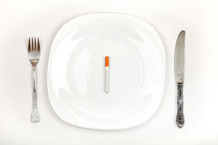 Sigaretta sul piatto di pranzo Immagini Stock