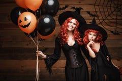 Concetto della strega di Halloween - madre allegra e sua la figlia in costumi della strega che celebrano Halloween che posa con l Immagini Stock