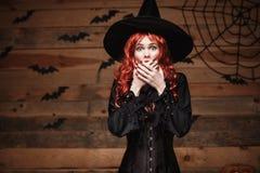 Concetto della strega di Halloween - tenuta rossa felice della strega dei capelli di Halloween che posa con il fronte colpito sop immagini stock