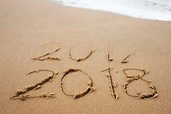 Concetto delle feste Il buon anno 2018 sostituisce 2017 sulla spiaggia del mare Immagine Stock