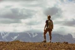 Concetto delle montagne di viaggiatore con zaino e sacco a pelo dell'uomo Fotografia Stock