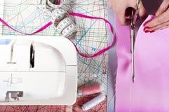Concetto dello stilista Le mani della donna che tagliano tessuto rosa in st fotografia stock