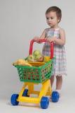 Concetto di acquisto - bambino con il carrello di acquisto Immagine Stock