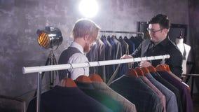 Concetto di acquisto Il venditore aiuta un giovane a scegliere un vestito nel deposito archivi video