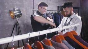 Concetto di acquisto Il venditore aiuta un giovane a scegliere un vestito nel deposito stock footage