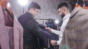 Concetto di acquisto Il venditore aiuta un giovane a scegliere un vestito nel deposito video d archivio