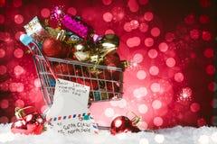 Concetto di acquisto di Natale, un carretto in pieno del regalo e una lettera alla decorazione del Babbo Natale, su neve, contro  immagini stock libere da diritti