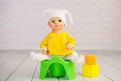 Concetto di addestramento a usare il vasino facendo uso di un potty del giocattolo e della bambola Fotografia Stock