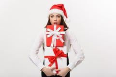 Concetto di affari - bella giovane donna caucasica di affari con il cappello di Santa che tiene molti contenitori di regalo con s Fotografia Stock Libera da Diritti