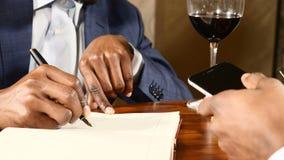 Concetto di affari Colpo alto vicino delle mani afroamericane maschii sulla tavola con un posto del fuoco su fondo Affare stock footage