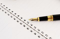 Concetto di affari con la penna stilografica alle pagine del libro del pianificatore fotografia stock