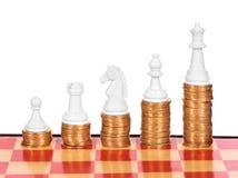 Concetto di affari con scacchi e le monete Immagini Stock